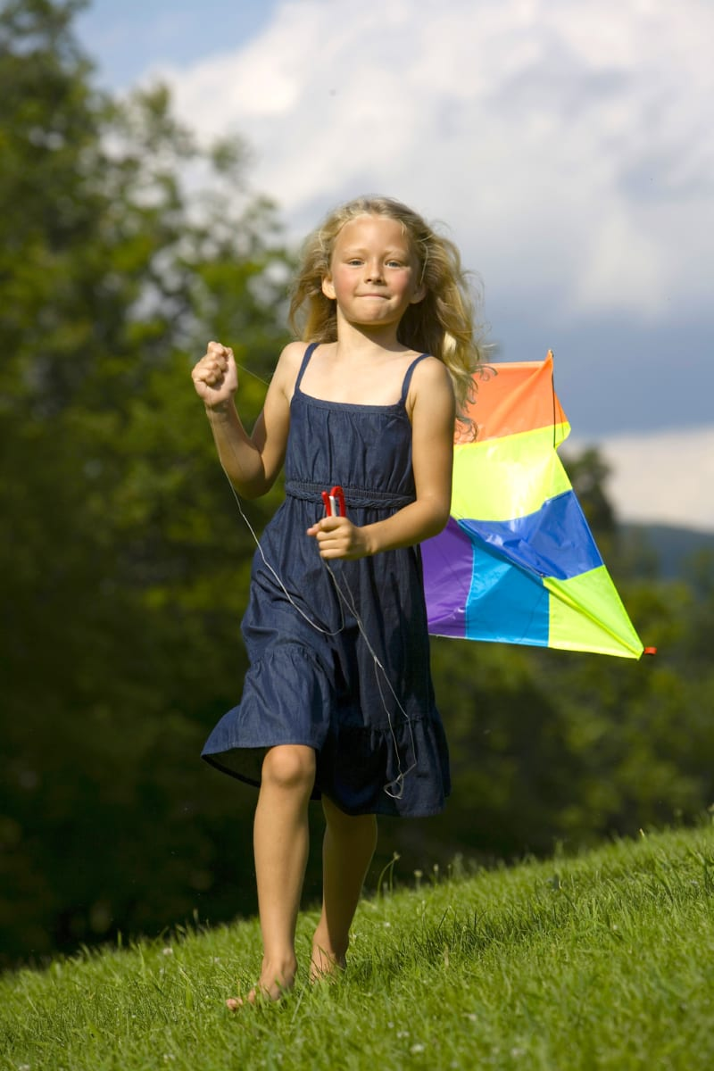 Girl running with a kite.