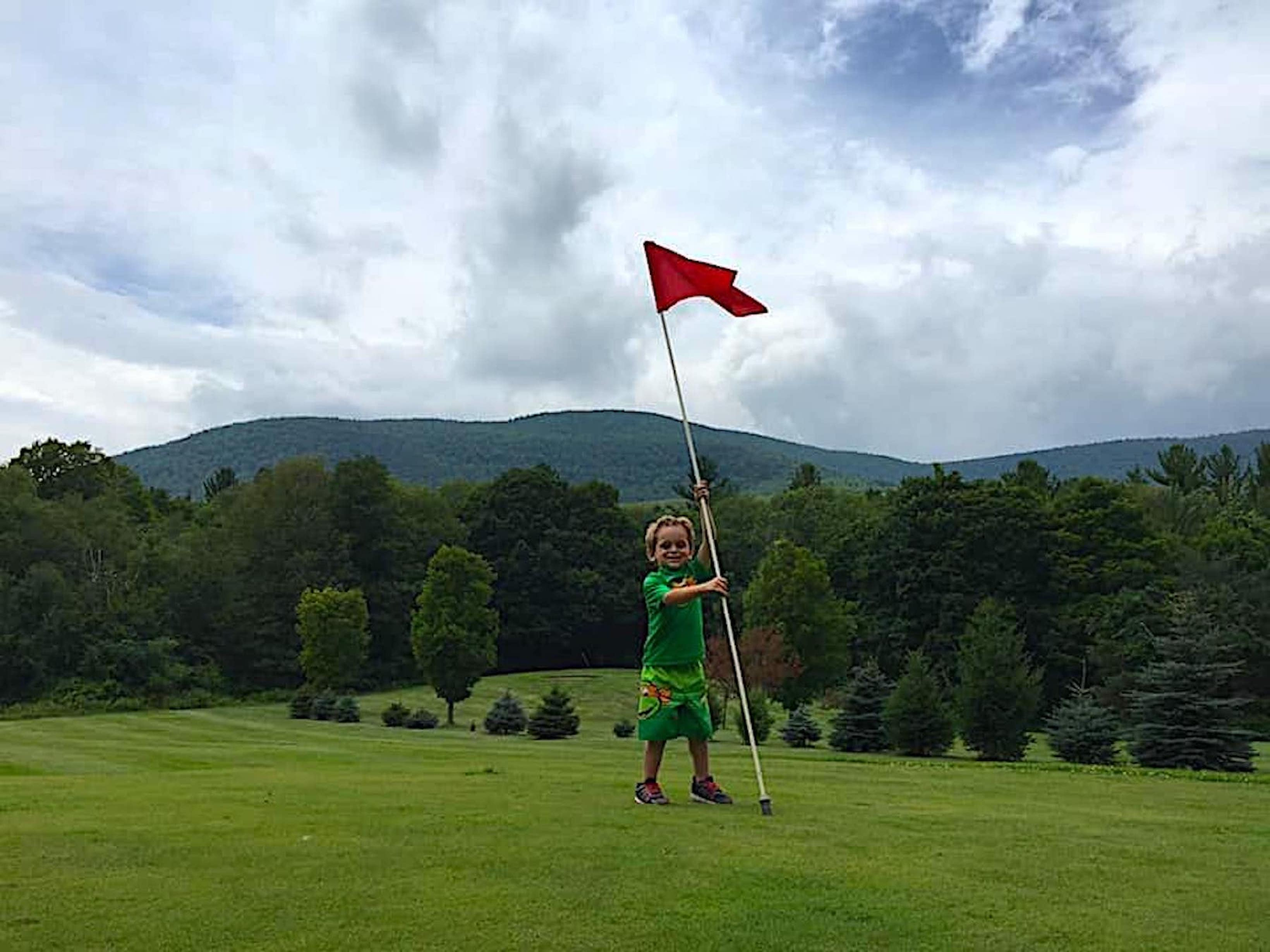 Young boy holding a golf flag.