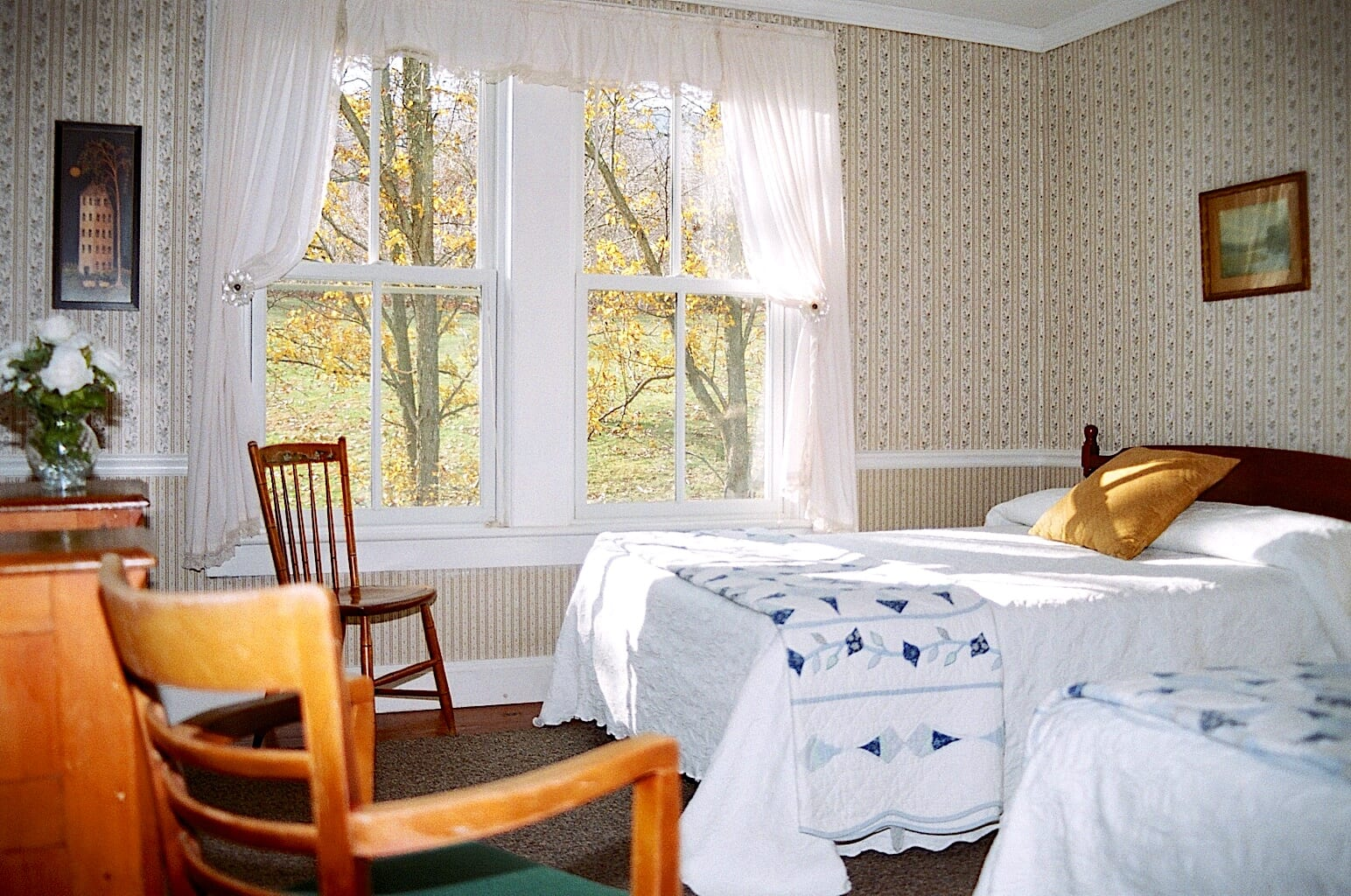 Bedroom at Winter Clove Inn with two double beds and large window.