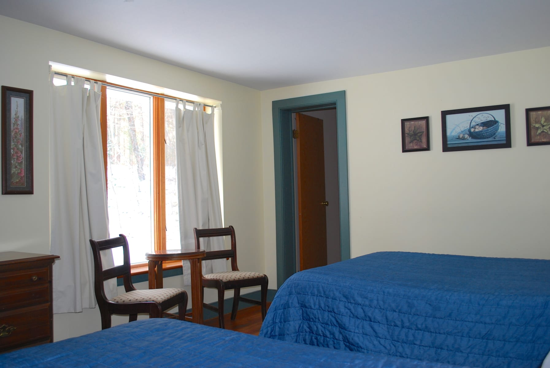 resort bedroom with two double beds and window.