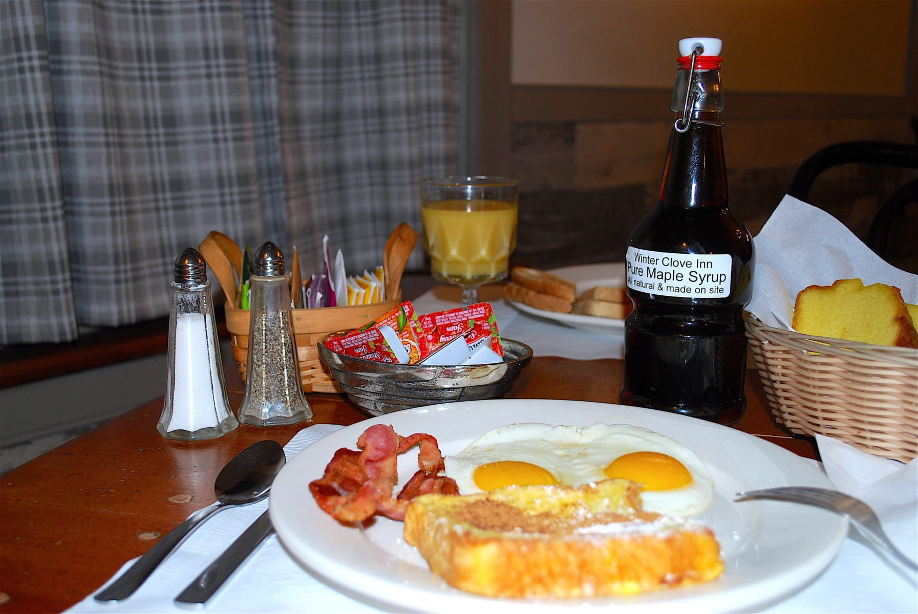 Full country breakfast with eggs, french toast, and syrup.