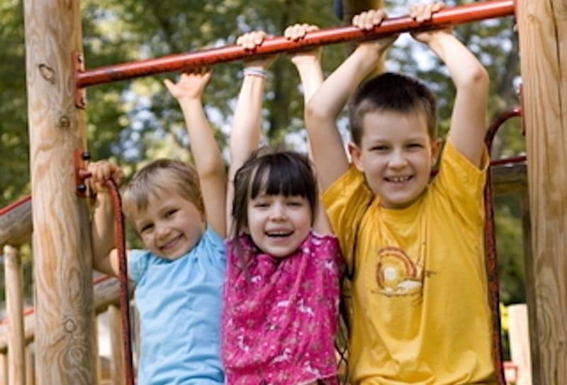 Three kids hanging on a playground.