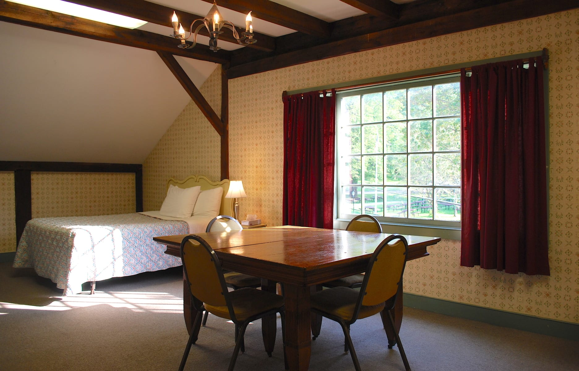 Hotel bedroom with bed, large table and windows.