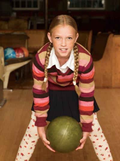 girl bowling with stripped shirt