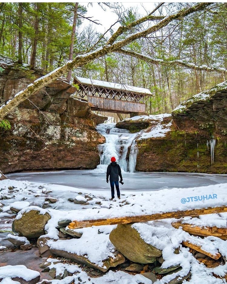 Person looking at frozen waterfalls with covered bridge
